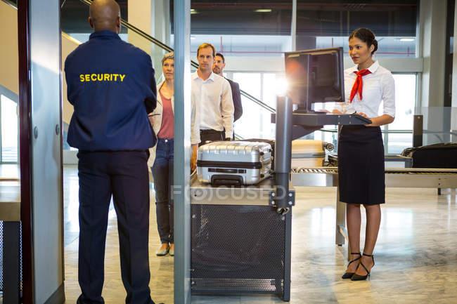 Аеропорт охоронця з пасажирами, проходячи через тіло сканер в термінал — стокове фото