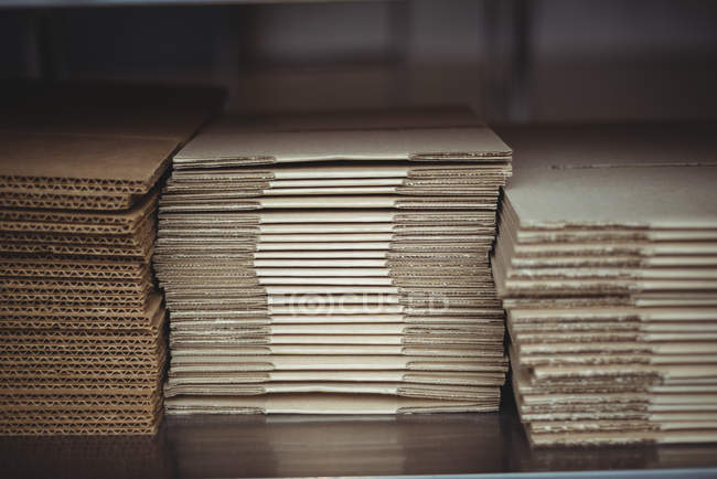 Stack of corrugated board on table in office — Stock Photo
