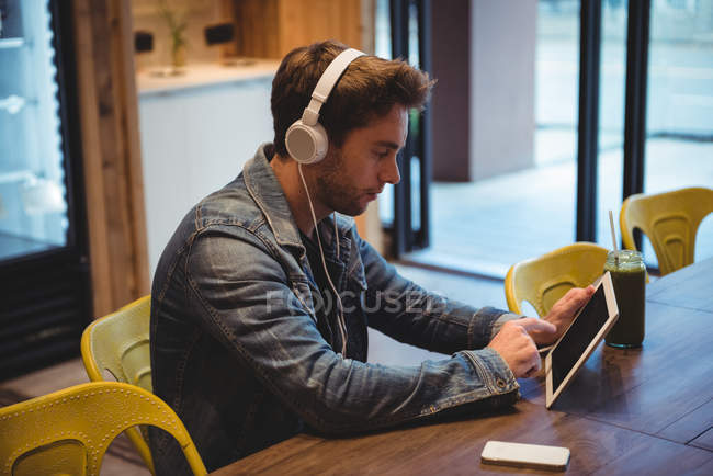 Man listening to music with headphones while using digital tablet in cafe — Stock Photo
