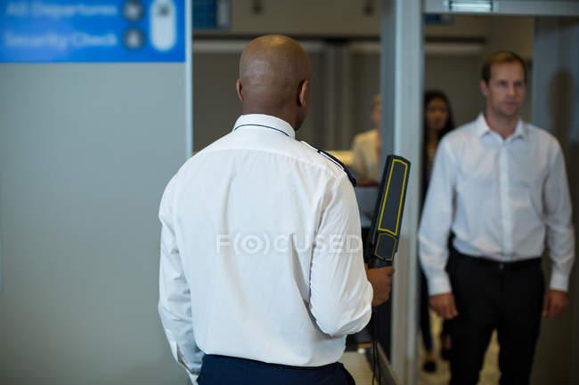 Oficial de seguridad del aeropuerto de pie con detector de metales para comprobar un viajero en el aeropuerto - foto de stock