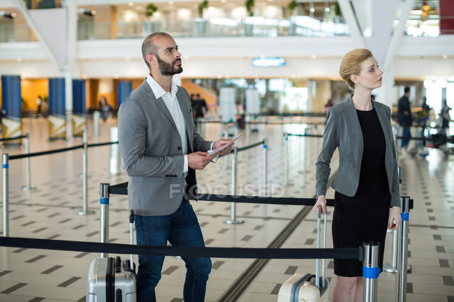 Empresários esperando em fila no balcão de check-in com bagagem no terminal do aeroporto — Fotografia de Stock