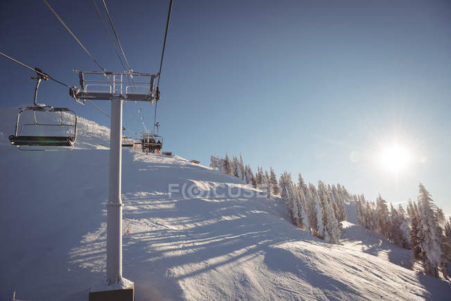 Ski lift in the ski resort against blue sky with people in background — Stock Photo