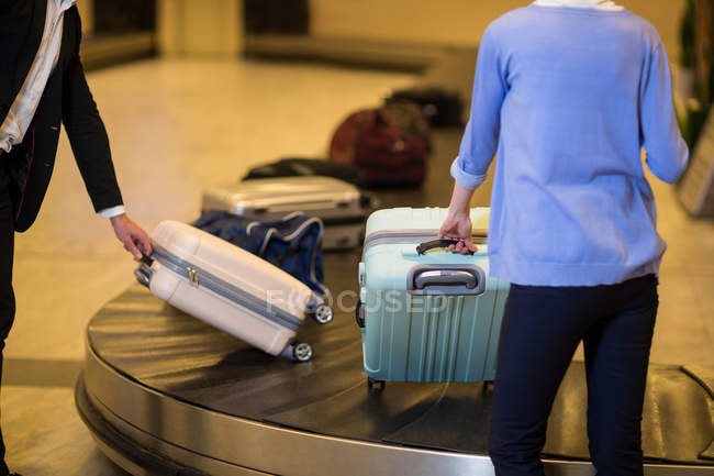 Commuters picking his luggage from baggage claim area at airport — Stock Photo