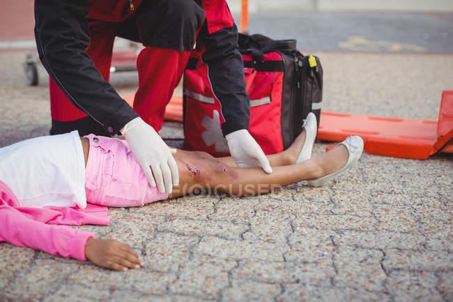 Парамедиків вивчення поранення дівчина на вулиці — стокове фото