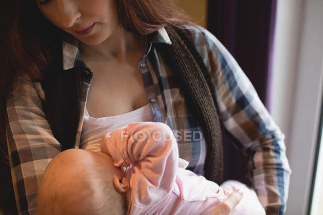 Close-up of mother breastfeeding newborn baby at home — Stock Photo