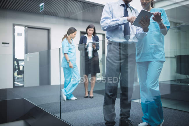 Doctors and nurses discussing over digital tablet in hospital corridor — Stock Photo