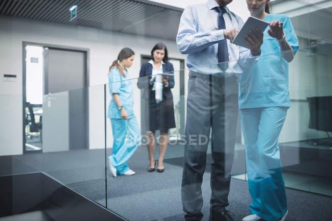 Врачи и медсестры обсуждают цифровые таблетки в коридоре больницы — стоковое фото