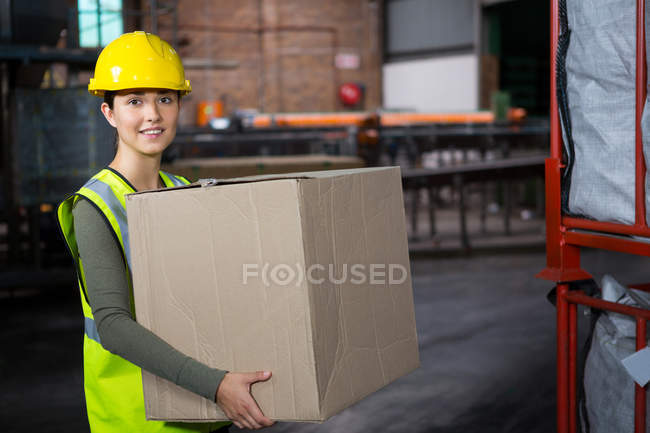 Portrait of beautiful female worker carrying box in warehouse - foto de stock
