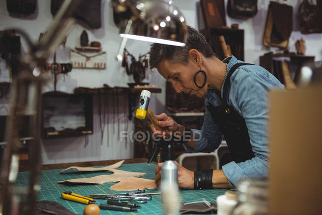Mature craftswoman hammering leather in workshop — Stock Photo