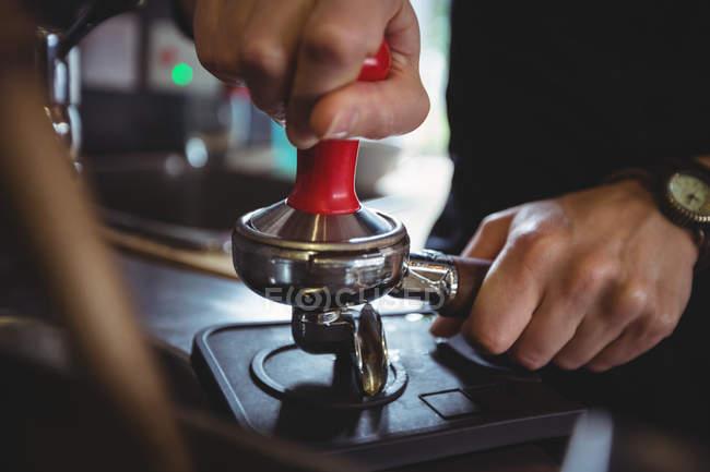 Закри використання в tamper натиснути меленої кави в portafilter в кафе офіціанткою — стокове фото