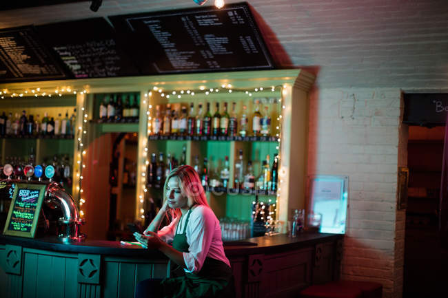 Thoughtful waitress sitting at counter in bar — Stock Photo