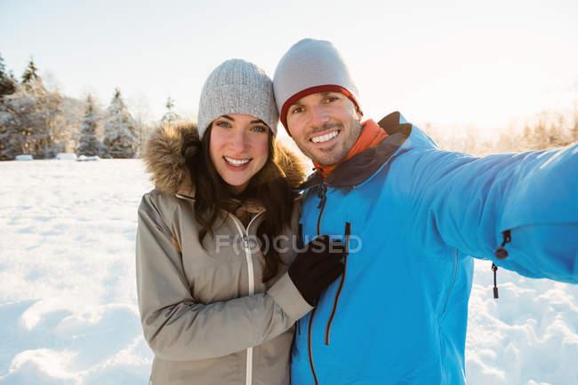 Портрет счастливой пары, делающей селфи на снежном ландшафте — стоковое фото