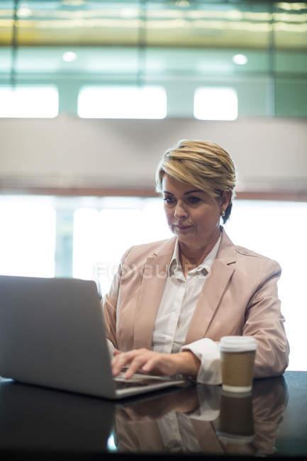 Підприємець, використовуючи ноутбук у зону очікування в аеропорту терміналу — стокове фото