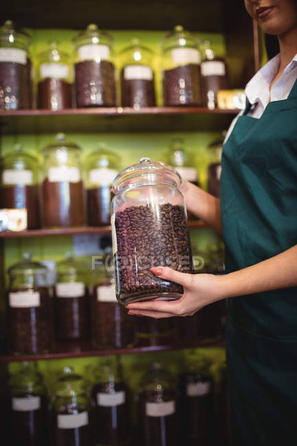 Mid section of female shopkeeper holding jar of coffee beans at counter in shop — Stock Photo