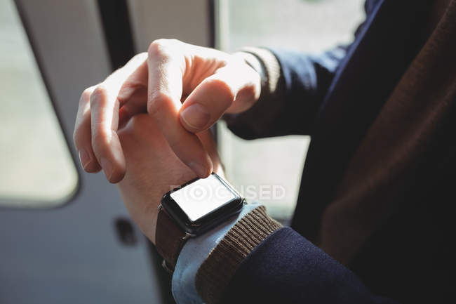 Mid-section of businessman using smartwatch while travelling in train — Stock Photo
