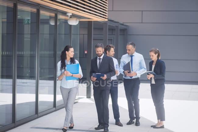 Groupe de gens d'affaires marchant à l'extérieur du bâtiment de bureaux — Photo de stock
