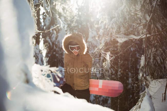 Femme avec snowboard marchant sur la montagne enneigée — Photo de stock