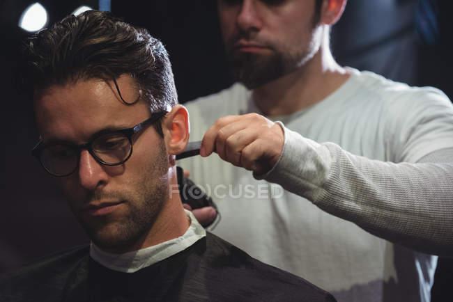 Hombre consiguiendo pelo recortado por peluquería con trimmer en peluquería - foto de stock