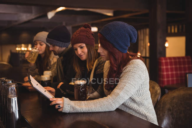 Friends having beer and holding menu at bar counter — Stock Photo