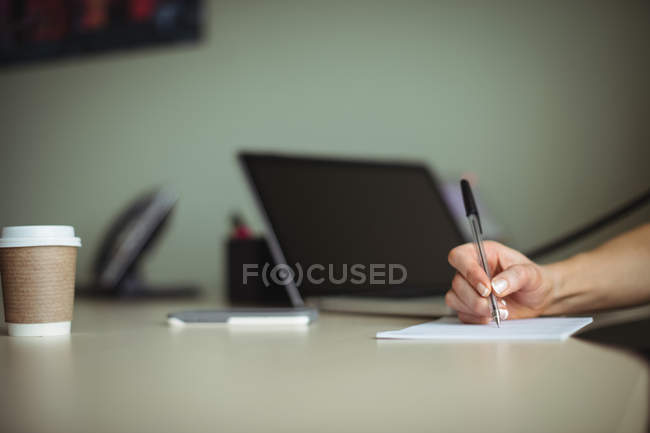 Hand of businesswoman writing on notepad in office — Stock Photo
