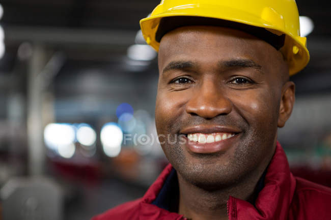 Close up portrait of male worker wearing yellow hard hat at factory — Stock Photo