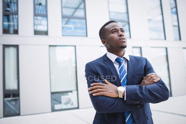Thoughtful businessman with arms crossed standing outside office building — Stock Photo