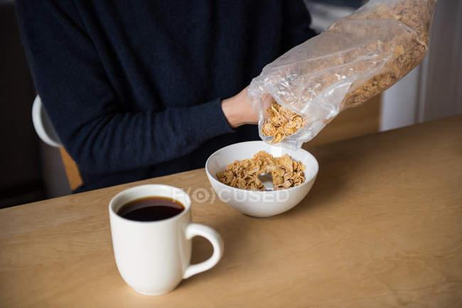 Sezione centrale dell'uomo versare i cereali in ciotola a casa — Foto stock