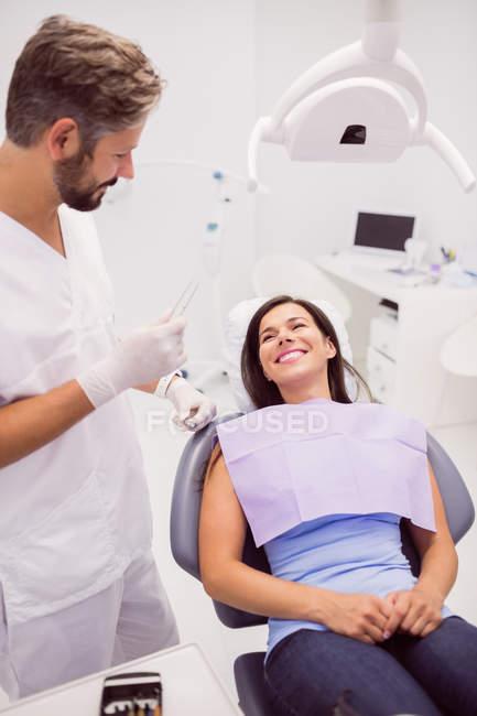Dentista parlando con sorridente paziente femminile sdraiato sulla sedia in clinica — Foto stock