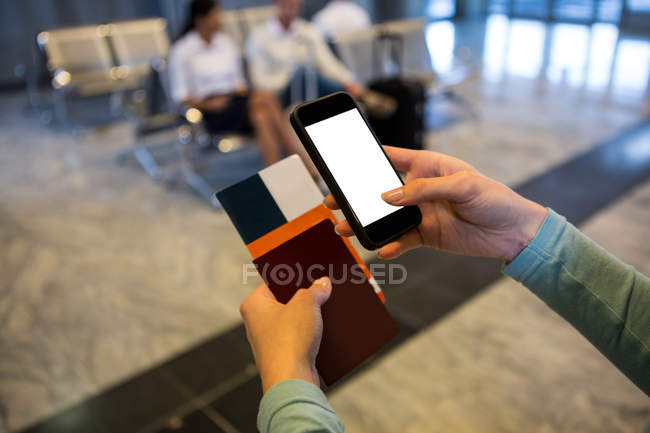 Female hands holding smartphone, passport and boarding pass at airport terminal — Stock Photo