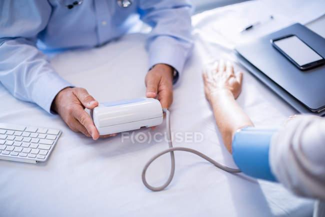 Recortar imagen de comprobación de la presión arterial del paciente en la clínica del Doctor - foto de stock
