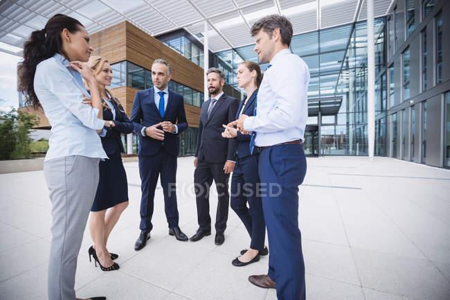 Група веселий бізнесменів взаємодії поза Офісна будівля — стокове фото