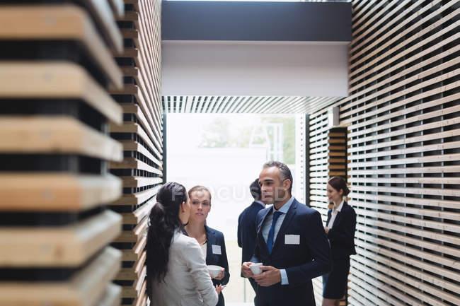 Geschäftsleute mit Tee und Interaktion während der Pause im Büro — Stockfoto