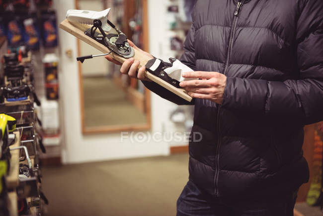 Close-up of man selecting ski binding in a shop — Stock Photo