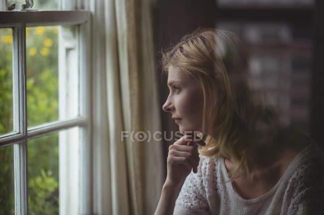 Bella donna guardando attraverso la finestra a casa — Foto stock