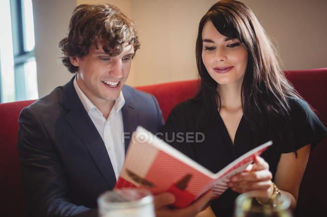 Paar mit Menü in modernem Restaurant — Stockfoto