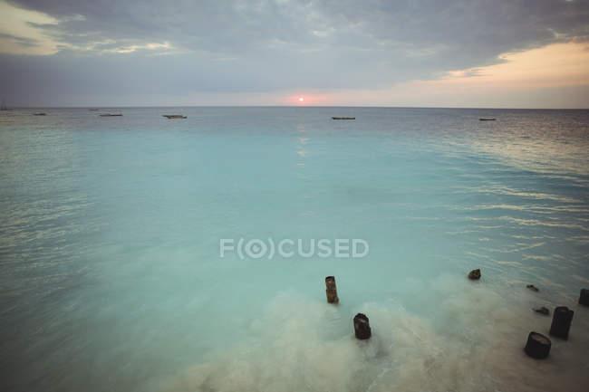 Alte Holzpfähle im Meer bei Sonnenuntergang — Stockfoto