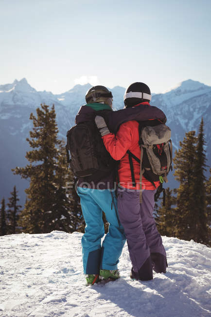 Rear view of two skiers standing together with arm around on snow covered mountain — Stock Photo
