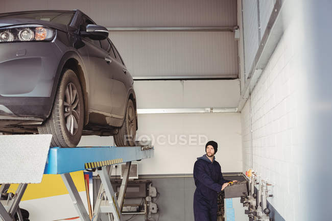 Механік за допомогою керування поля в ремонт гаража — стокове фото