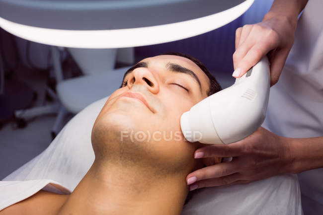 Mann bekommt Gesichtsmassage für kosmetische Behandlung in Klinik — Stockfoto