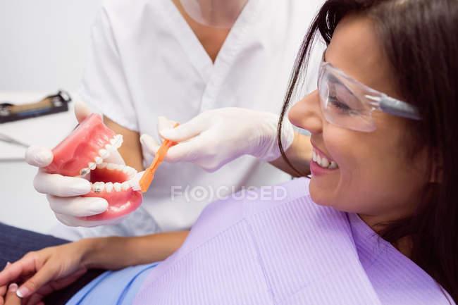 Dentiste montrant le modèle de dents à la patiente en clinique dentaire — Photo de stock