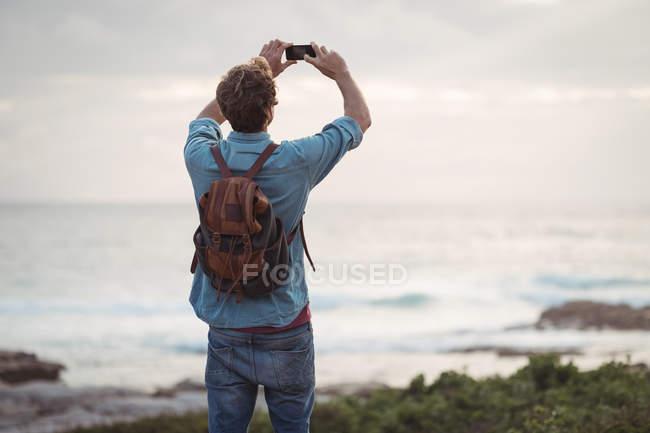 Rückansicht eines Mannes, der mit dem Handy fotografiert — Stockfoto