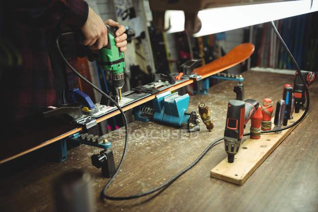 Primo piano dell'uomo che fissa gli attacchi da sci sugli sci con un trapano — Foto stock