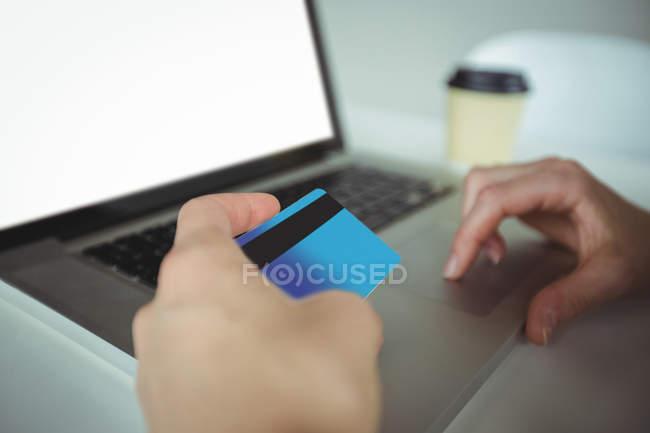 Жінка робить онлайн-платежів за допомогою ноутбук і кредитної картки в кафе — стокове фото