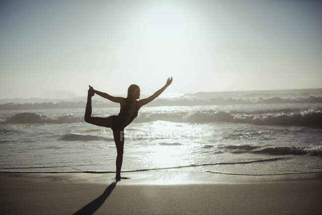 Woman performing yoga on beach at dusk — Stock Photo
