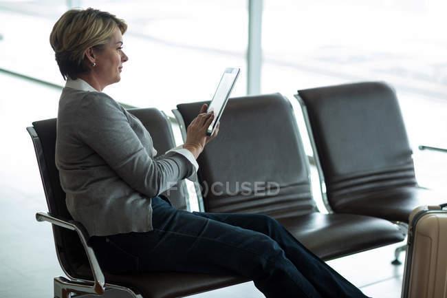 Donna d'affari che utilizza tablet digitale in sala d'attesa presso il terminal dell'aeroporto — Foto stock