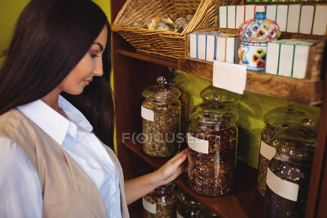 Hermosa mujer mirando frascos de especias en la tienda - foto de stock