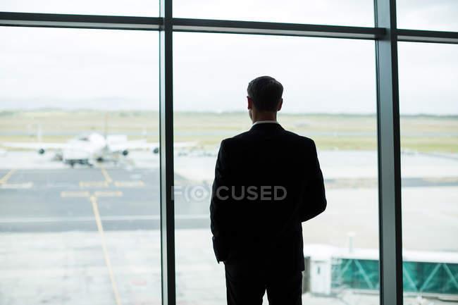 Rückansicht des Kaufmanns Blick durch Fenster im Wartebereich am Flughafen — Stockfoto