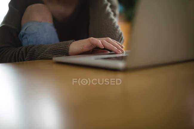 Sección media de la mujer que usa el ordenador portátil en la mesa en casa - foto de stock