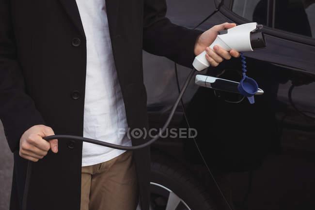 Partie médiane de l'homme tenant chargeur de voiture — Photo de stock
