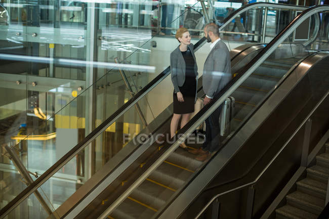 Business people interacting with each other while going up on escalator at airport terminal - foto de stock